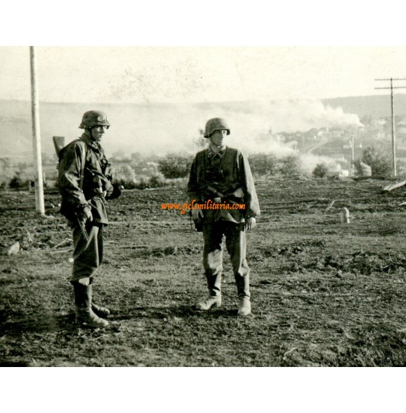 SS troops, camouflage , burned down city